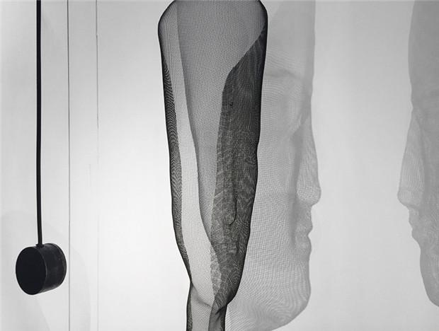 随着光源缓缓移动,钢丝网人形在墙壁上投射出戏剧化的影子,呈现出极具